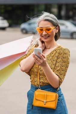 trendy middle aged woman with shopping bags looking at cellphone on street