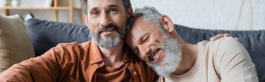 Homosexual man embracing smiling partner at home, banner