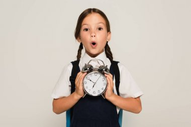 astonished schoolkid showing large alarm clock isolated on grey