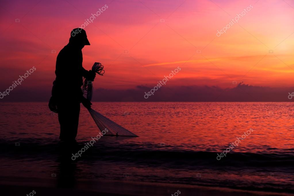 Silhouettes fisherman casting at the sea.