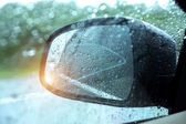 Abstract image of rain drops on car side view mirror and window.