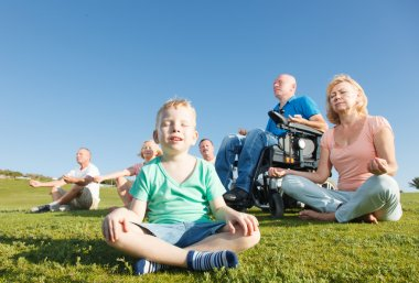 Disabled Man with family practicing yoga outside.
