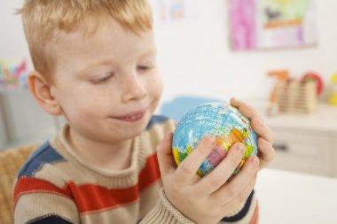 Preschooler with globe in a hand