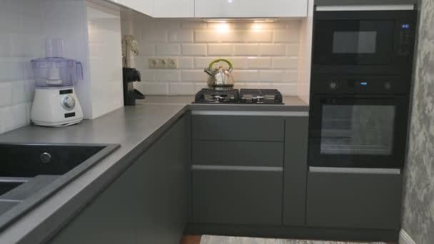 Detailní záběr moderního bílého a šedého kuchyňského interiéru, pohyb sklopné kamery
