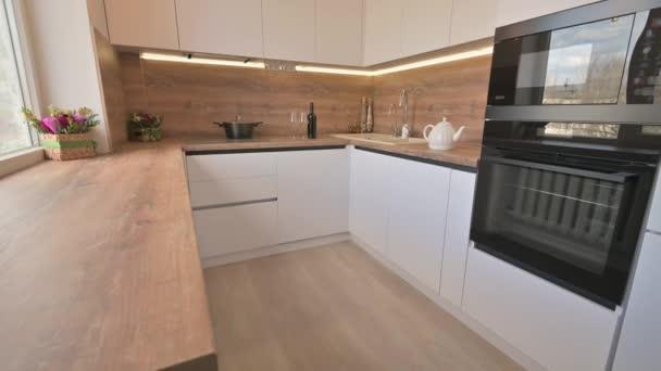 Širokoúhlý náklon záběr moderní bílé a dřevěné béžové kuchyně interiér