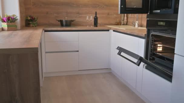 Széles látószögű billenő lövés a modern fehér és fa bézs konyha belső