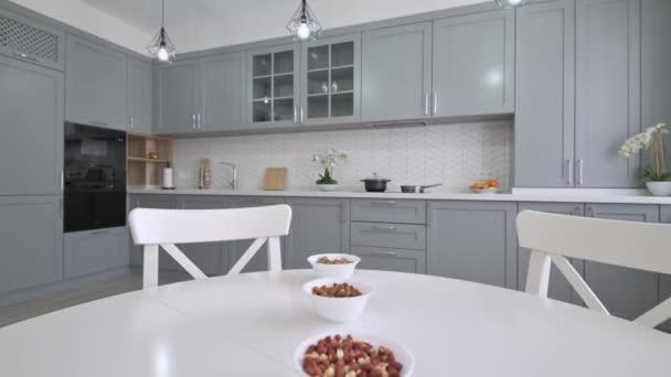 Velký luxusní moden klasická šedá kuchyně s bílým jídelním stolem