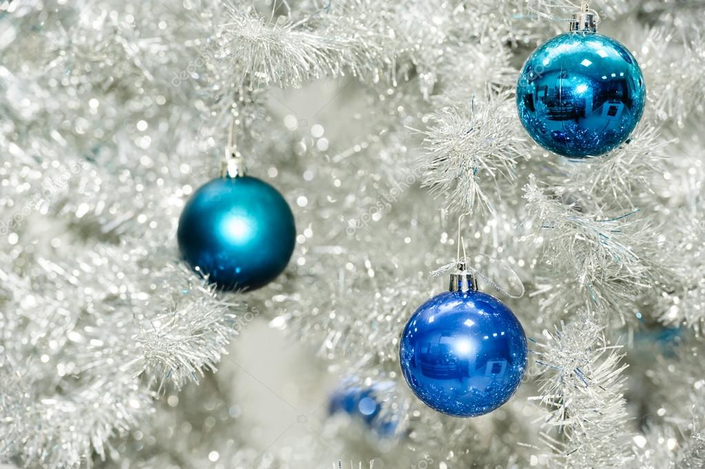 Blue baubles on silver artificial christmas tree