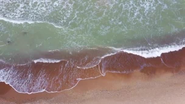 Légi Dron Shot a Balti-tenger Costline Hullámok Kilátás felülről. Tengeri hullámok egy Sandy Beach felett. Top Kilátás a tengeri hullámok habzó és fröccsenő, Big Waves felülről. 4K videó