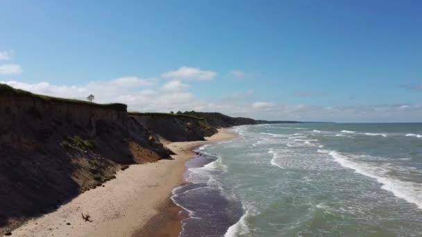 Ulmale Seashore Bluffs in der Nähe von Pavilosta, Lettland und Erdrutsche mit einer überwucherten, plätschernden Höhle, gespickt mit Klippen und Kieselsteinen. Dronenblick aus der Luft. Kamera rückt 4K-Video vor