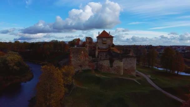 Bauska középkori kastély romjai komplexum és Park felülről légi lövés. Romok a Livonian része a Bauska vár, Lettország ősszel. Castle épült a közepén a 15. században