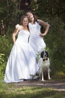 just married lesbian pair with dog in forest
