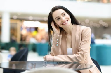 Smiling happy woman is sitting in cafe