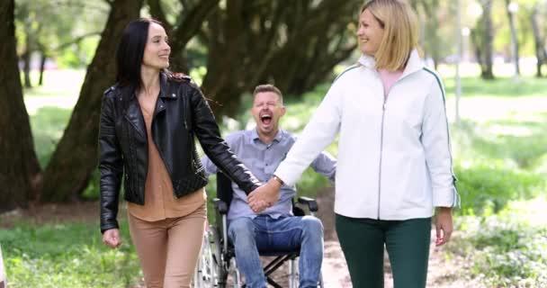 Mann im Rollstuhl schreit und versucht, zwei Frauen einzuholen 4k Film