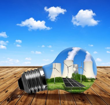 Nuclear power plant with solar panel and wind turbines in lightbulb.