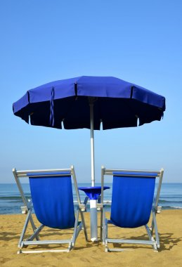 Sun loungers and umbrella on a sandy beach.