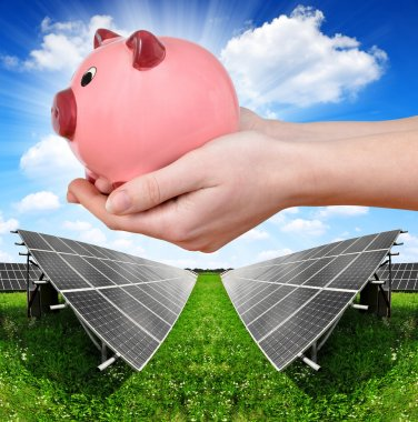 Solar panels and hand holding a pink piggy bank.