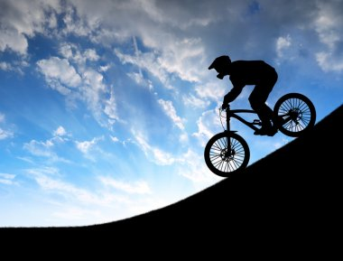 Silhouette of the cyclist on downhill bike
