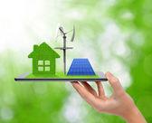 Tablette mit Gewächshaus, Windkraftanlage und Solaranlage.