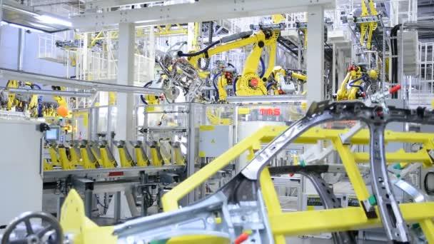 Pracovní žluté robotické paže v továrně Škoda Auto