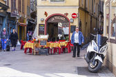 Fotografie Nice, France, on March 13, 2015. Little tables of street cafe in Provencal style in the old city