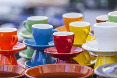Bright coffee cups of various colors on a show-window of shop
