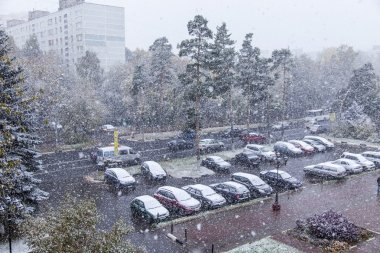 PUSHKINO, RUSSIA - on OCTOBER 8, 2015. First snow. A blizzard in the city. A view of the street and an automobile parking in the inhabited massif