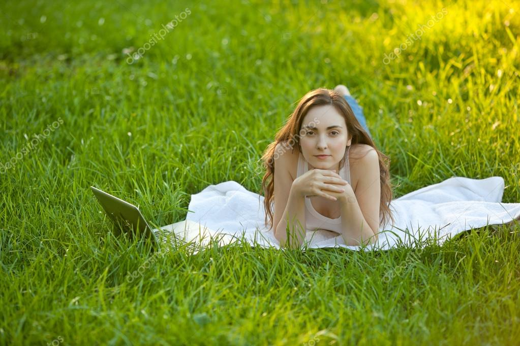 Woman relaxing lying on green grass