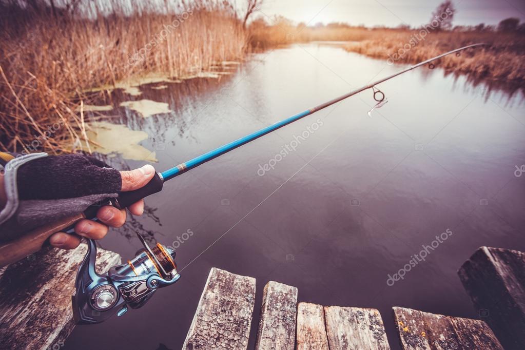 Человек, держащий спиннинг на реке. Рыбалка — Стоковое фото ...