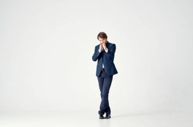 Gentleman in a suit on a light background gestures with his hands work business finance model