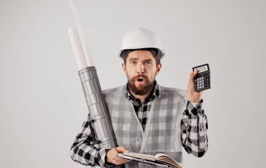 A builder in a helmet with a tube in his hands a blueprint on a light background paper