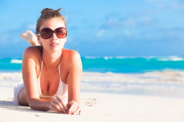 young girl in bikini and round sunglasses on tropical barbados beach