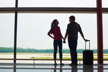 couple holding hands and waiting at airport terminal