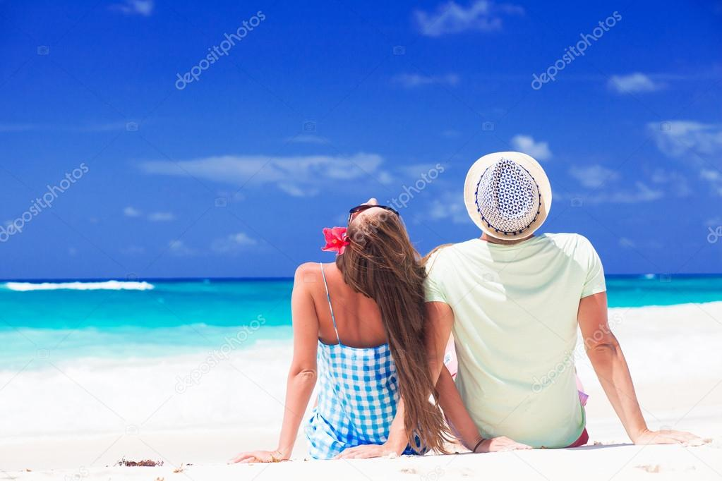 Romantic couple in bright clothes enjoying sunny day at tropical beach