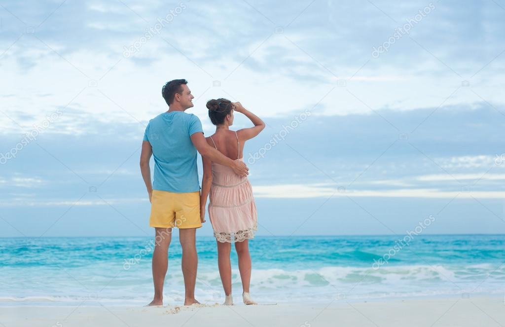 Back view of couple in bright clothes having fun at tropical beach