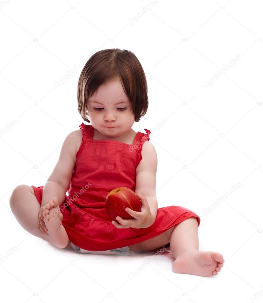 0db5526ff8d Baby girl in red dress isolated on a white background playing with red apple  — Photo by ...