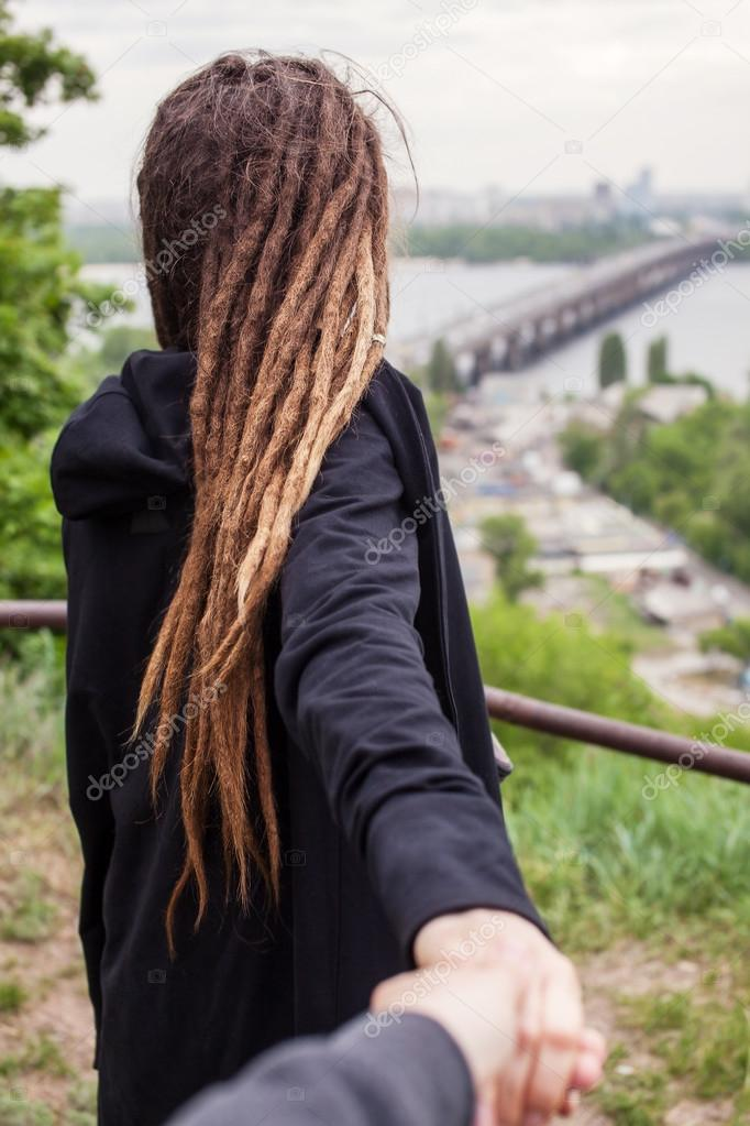 The guy holding girl with dreadlocks in black hand on a background of Kyiv city