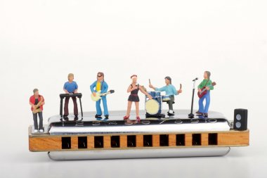 Miniature of a rock band performing on a big harmonica