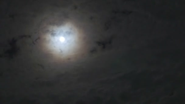 Time lapse of the moon glowing behind the clouds