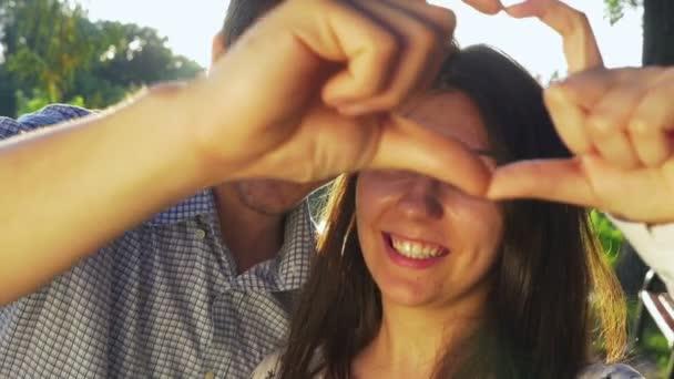 Detail mladého páru, provedení tvaru srdce při západu slunce a líbání