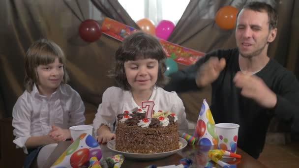 Krásná mladá dívka, foukání svíčky na narozeninový dort s její otec a dvojče sestry, zpomalené