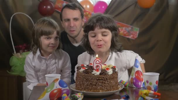 Young beautiful girl blowing candles on a birthday cake with her father and twin sister, slow motion