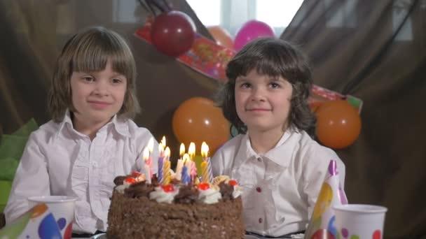 Mladé krásné dvojče sestry foukání svíčky na narozeninový dort, zpomalené