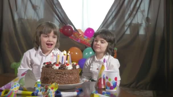 Krásná mladá dívka, foukání svíčky na narozeninový dort s její dvojče