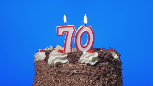 Foukání číslo sedmdesát narozeninové svíčky na lahodný čokoládový dort, modrá obrazovka