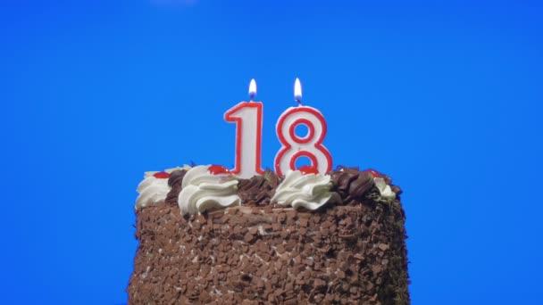 Foukání číslo osmnáct narozeninové svíčky na lahodný čokoládový dort, modrá obrazovka