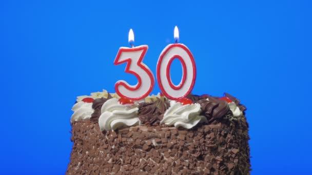 Foukání číslo třicet narozeninové svíčky na lahodný čokoládový dort, modrá obrazovka