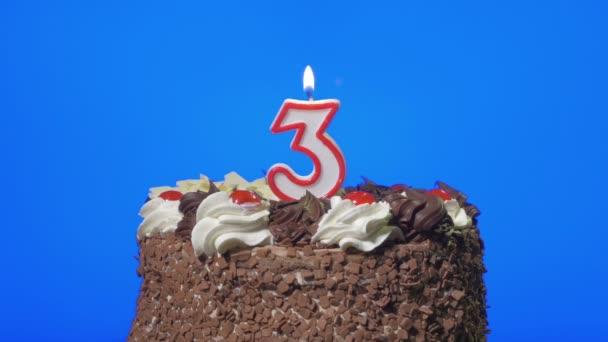 Foukání číslo tři narozeninovou svíčku na lahodný čokoládový dort, modrá obrazovka