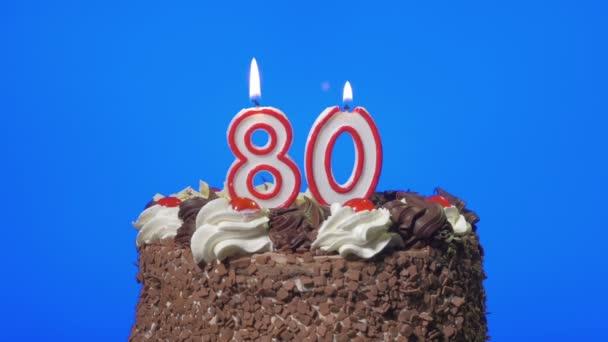Che soffia fuori numero ottanta compleanno candele sullo schermo deliziosa torta al cioccolato, blu