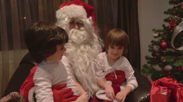 Mladé krásné dvojče dívky sedící na klíně Ježíška na Štědrý den - 4k